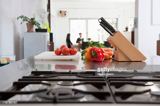 Tomatoes, carrots and bell peppers on a kitchen counter