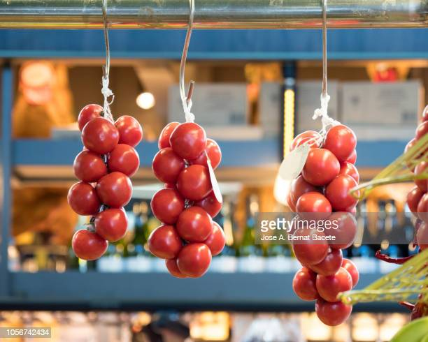 tomatoes hanging in an indoor market stall, grown ecologically. - valencia spanje stockfoto's en -beelden