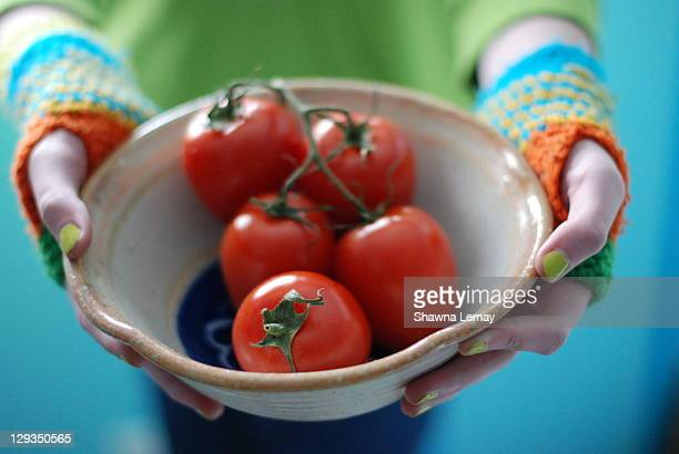 tomatoes in bowl - 指なし手袋 ストックフォトと画像