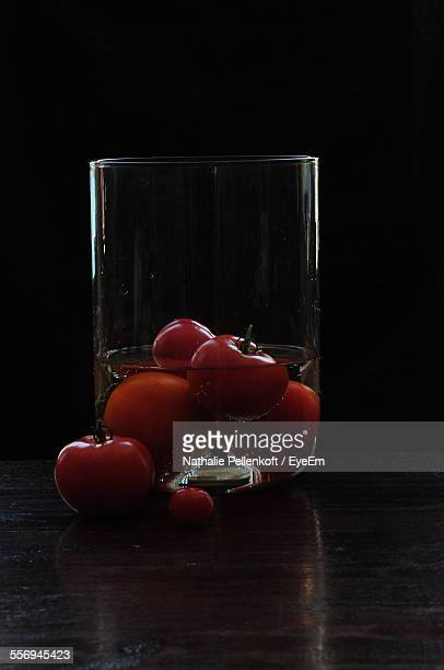 tomatoes in glass on table against black background - nathalie pellenkoft stock pictures, royalty-free photos & images