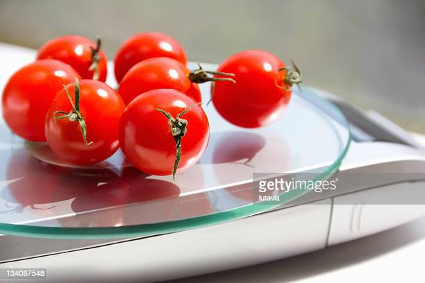 tomatoes on the kitchen scales - lutavia stock pictures, royalty-free photos & images