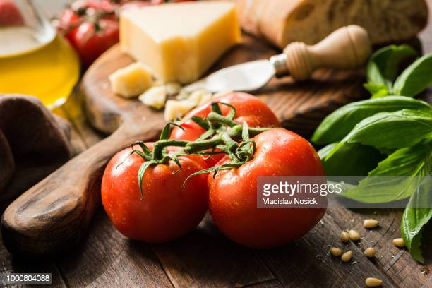 Tomatoes on vine, olive oil and parmesan cheese, food background