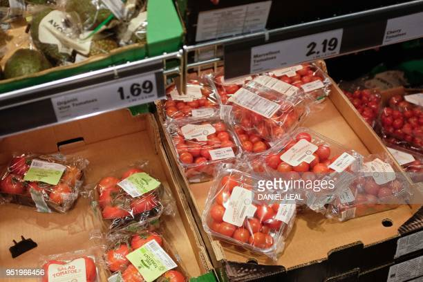 Tomatoes packaged in plastic are pictured in a supermarket in north London, on April 27, 2018. - 42 firms, responsible for 80 percent of plastic...