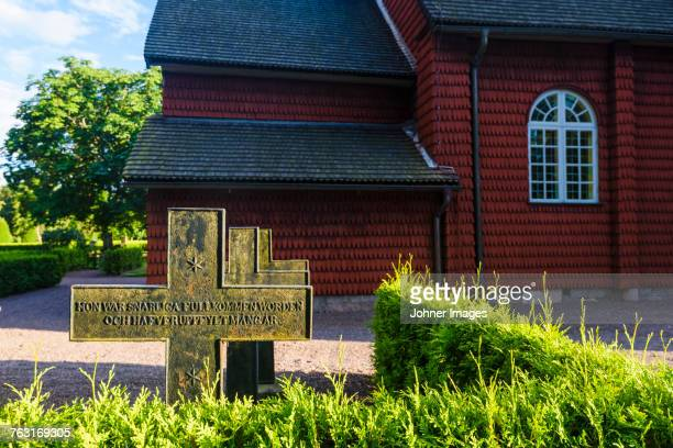 Tombstone in front of wooden church