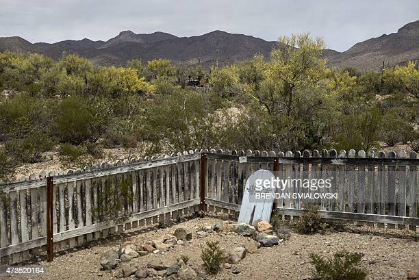 A tombstone is seen as a train passes in the background at the Old Tucson Studios in Tucson Arizona on May 15 2015 Old Tucson Studios was once...