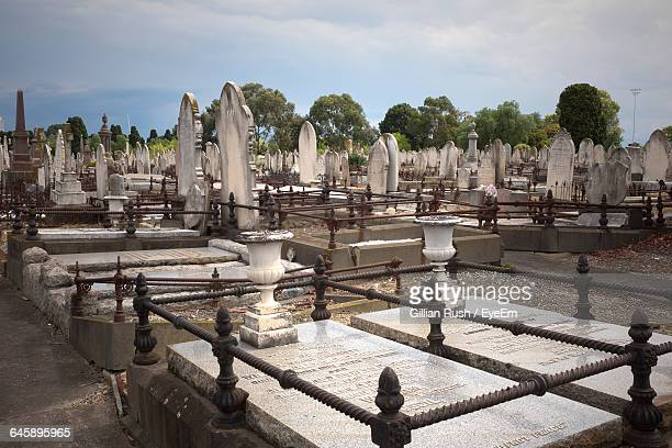 Tombstones In Cemetery Against Sky On Sunny Day