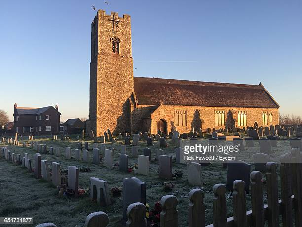 tombstones in cemetery by church against sky - east anglia stock pictures, royalty-free photos & images