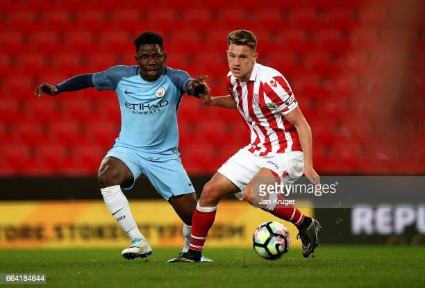 Tome DeleBashiru of Manchester City battles with Jake Dunwoody of Stoke City during the FA Youth Cup Semi Final second leg match between Stoke City...