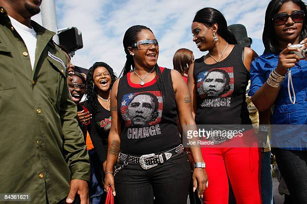 Tomeka Jackson and Chenesia Harris wear shirts with pictures of Presidentelect Barack Obama on them as they watch a parade pass by in honor of Dr...