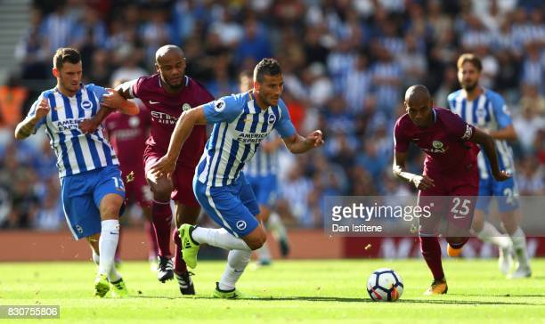 Tomer Hemed of Brighton and Hove Albion attempts to get away from Fernandinho of Manchester City and Vincent Kompany of Manchester City during the...