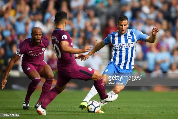 Tomer Hemed of Brighton and Hove Albion attempts to get past Sergio Aguero of Manchester City during the Premier League match between Brighton and...