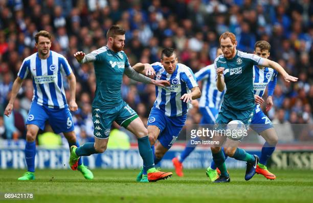 Tomer Hemed of Brighton and Hove Albion is challenged by Ryan Tunnicliffe and Shaun MacDonald of Wigan during the Sky Bet Championship match between...