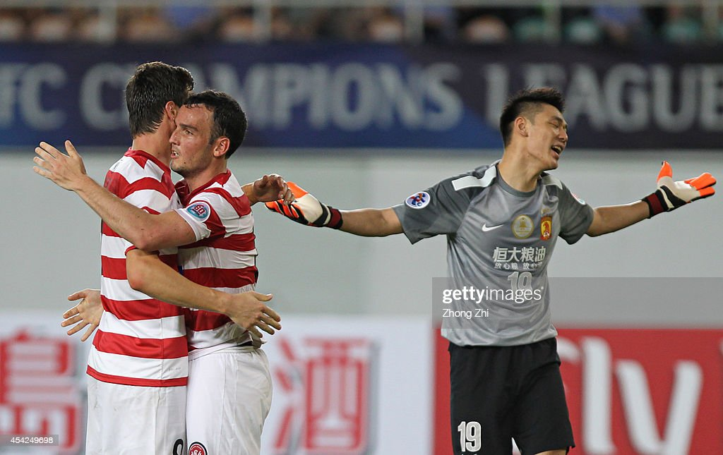 Tomi Juric and Mark Bridge of Western Sydney Wanderers celebrates winning a penalty while Zeng Cheng of Guangzhou Evergrande reacts during the Asian Champions League Quarter Final match between the Western Sydney Wanderers and Guangzhou Evergrande at Tianhe Sports Center on August 27, 2014 in Guangzhou, China.