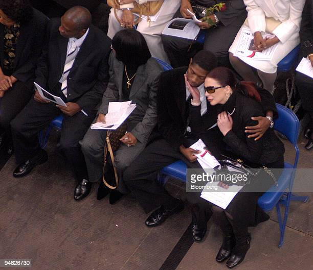 Tomi Rae Brown right with glasses receives comfort from one of James Brown's children during James Brown's funeral at the James Brown Arena in...