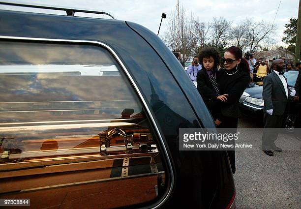 Tomi Rae Hynie and her son James Brown 2d look into a hearse containing the coffin of soul legend James Brown as it pulls away after a private...