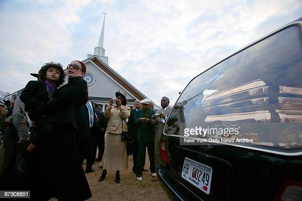 Tomi Rae Hynie holds her son James Brown 2d next to a hearse containing the coffin of soul legend James Brown as it pulls away after a private...