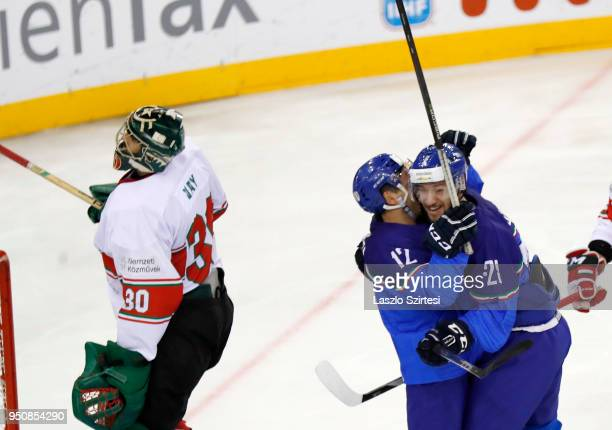 Tommaso Goi of Italy and Tommaso Traversa of Italy celebrate next to Adam Vay of Hungary during the 2018 IIHF Ice Hockey World Championship Division...