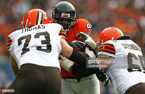 Tommie Harris of the Chicago Bears is doubleteamed blocked by Joe Thomas and Eric Steinbach of the Cleveland Browns at Soldier Field on November 1...
