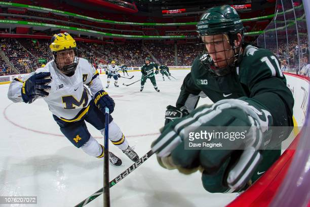 Tommy Apap of the Michigan State Spartans battles along the boards for the puck with Luke Martin of the Michigan Wolverines in the second period...