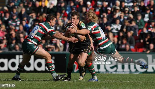 Tommy Bowe of the Ospreys is tackled by Craig Newby and Billy Twelvetrees during the Heineken Cup match between Leicester Tigers and Ospreys at...