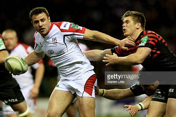 Tommy Bowe of Ulster fends off Owen Farrell and Ernst Joubert of Saracens during the Heineken Cup quarter final match between Saracens and Ulster at...