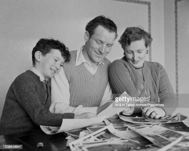 Tommy Briggs of Blackburn Rovers at home with his wife and son looking at photographs of his record for goals in a single match after scoring 7 goals...