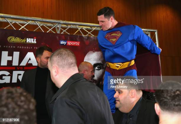 Tommy Coyle dressed as Superman jumps onto the desk during an Amir Khan and Phil Lo Greco press conference at the Hilton Hotel on January 30 2018 in...