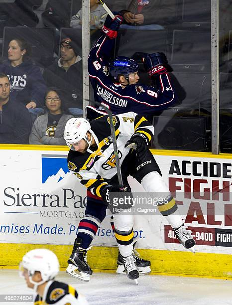 Tommy Cross of the Providence Bruins checks Henrik Samuelsson of the Springfield Falcons during an American Hockey League game at the Dunkin' Donuts...