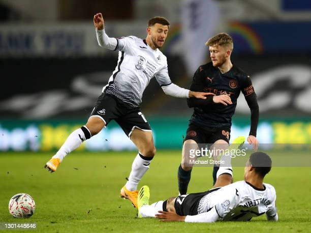 Tommy Doyle of Manchester City battles for possession with Paul Arriola and Morgan Whittaker of Swansea City during The Emirates FA Cup Fifth Round...