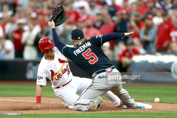 Tommy Edman of the St. Louis Cardinals returns to first base after a fly out and subsequently advances to second base on a throwing error by Nick...