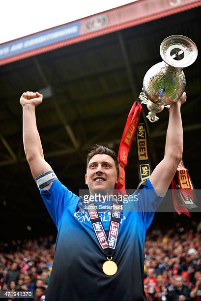 Tommy Elphick of AFC Bournemouth lifts the Championship trophy after winning the the Sky Bet Championship after the game between Charlton Athletic...