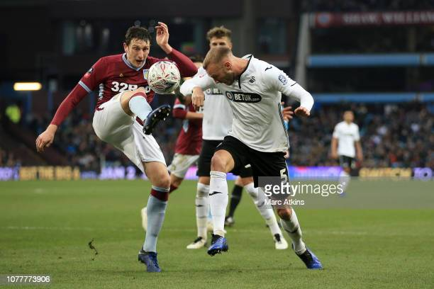 Tommy Elphick of Aston Villa battles for possession with Mike van der Hoorn of Swansea City during the FA Cup Third Round match between Aston Villa...