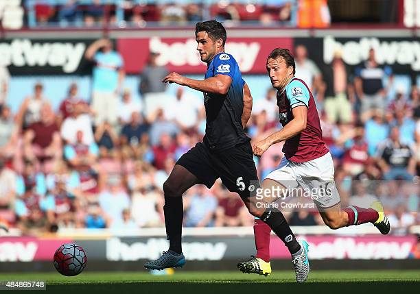 Tommy Elphick of Bournemouth and Mark Noble of West Ham United compete for the ball during the Barclays Premier League match between West Ham United...