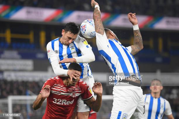 Tommy Elphick of Huddersfield Town heads the ball whilst under pressure by Ashley Fletcher of Middlesbrough during the Sky Bet Championship match...