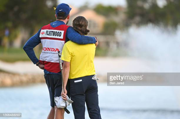 Tommy Fleetwood of England and his caddie hug on the 18th green during the final round of The Honda Classic at PGA National Champion course on March...