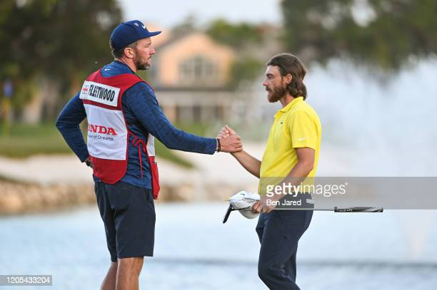 Tommy Fleetwood of England and his caddie shake hands on the 18th green during the final round of The Honda Classic at PGA National Champion course...