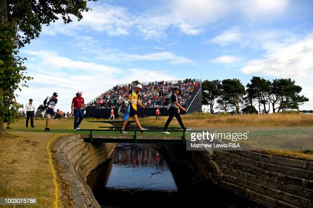 Tommy Fleetwood of England and Pat Perez of the United States walk over the bridge on the 11th hole during round three of the Open Championship at...