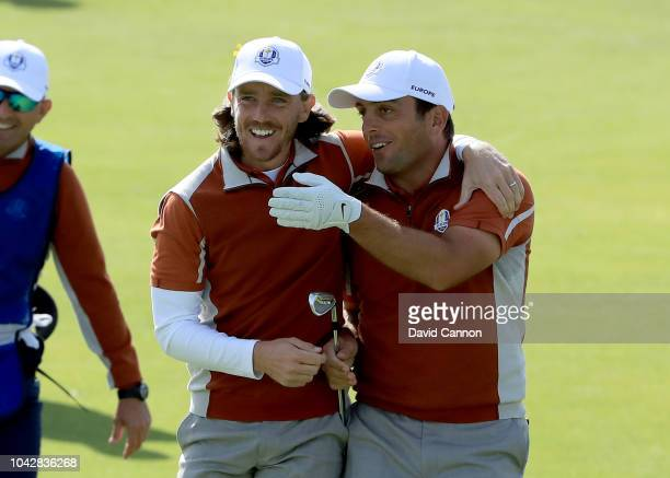 Tommy Fleetwood of England and the European Team embraces his partner Francesco Molinari after Molinari had hit a great shot to the 15th green which...