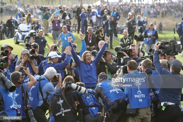 Tommy Fleetwood of England and the European Team is held aloft as he celebrates amongst a scrum of cameras after Europe's 17.5-10.5 win over the...
