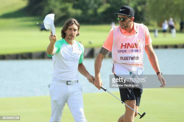 Tommy Fleetwood of England celebrates with hcaddie Ian Finnis on the 18th hole during the final round of the HNA Open de France at Le Golf National...