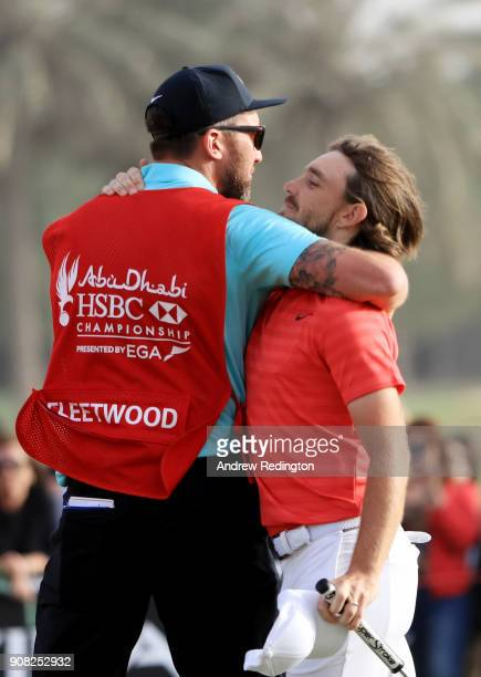 Tommy Fleetwood of England celebrates with his caddie Ian Finnis after putting for birdie on the 18th green to finish 22 under during the final round...