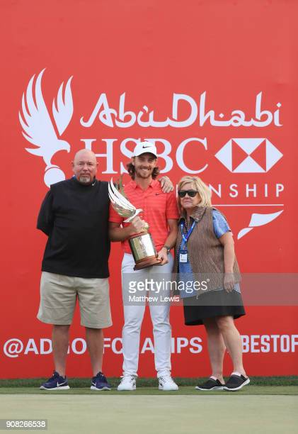 Tommy Fleetwood of England celebrates with his parents Pete and Sue and the trophy after winning during the final round of the Abu Dhabi HSBC Golf...