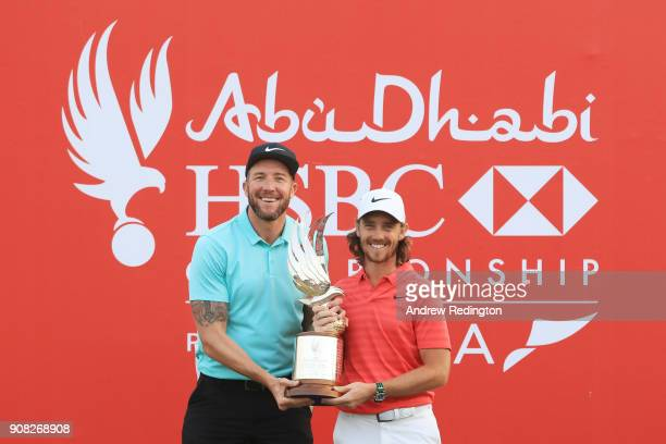 Tommy Fleetwood of England celebrates with the winner's trophy and caddie Ian Finnis after the final round of the Abu Dhabi HSBC Golf Championship at...