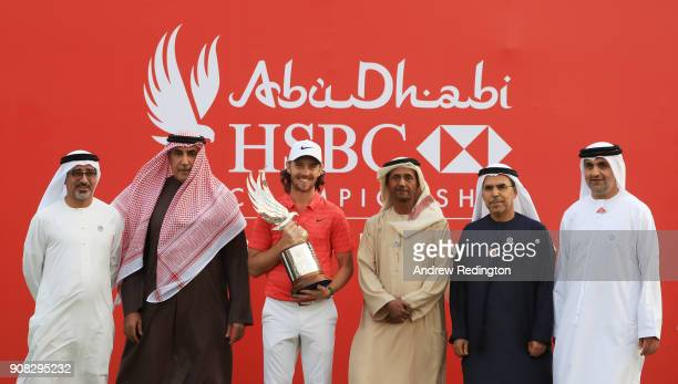 Tommy Fleetwood of England celebrates with the winner's trophy and Abdulfattah Sharaf CEO of HSBC in the UAE Major General Mohammed Khalfan Al...