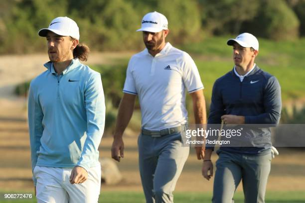 Tommy Fleetwood of England Dustin Johnson of the United States and Rory McIlroy of Northern Ireland walk on the 11th hole during round one of the Abu...