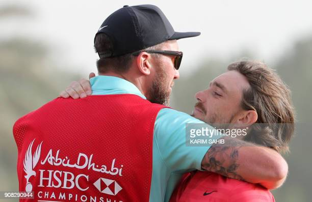 Tommy Fleetwood of England embraces his caddy Ian Finnis as they celebrate his victory at the Abu Dhabi HSBC Golf Championship at the Abu Dhabi Golf...