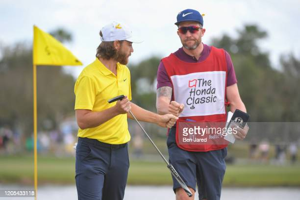 Tommy Fleetwood of England fist bumps his caddie while walking off the first green during the final round of The Honda Classic at PGA National...