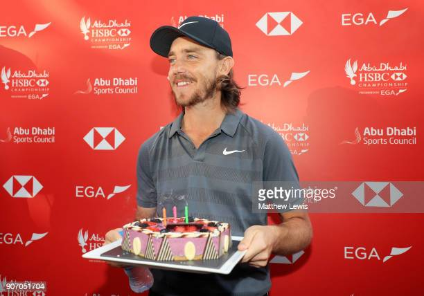 Tommy Fleetwood of England holds a cake presented to him by Rory McIlroy of Northern Ireland for his birthday after round two of the Abu Dhabi HSBC...