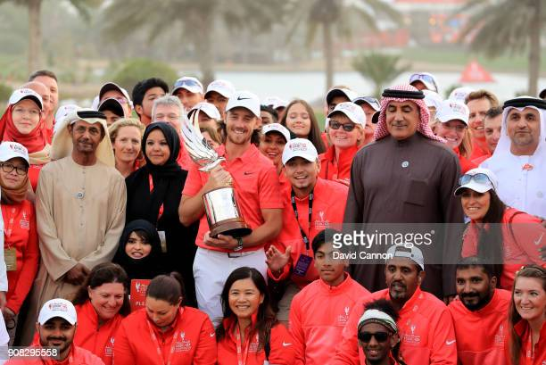 Tommy Fleetwood of England holds the Falcon Trophy amongst the volunteers after his win in the final round of the Abu Dhabi HSBC Golf Championship at...