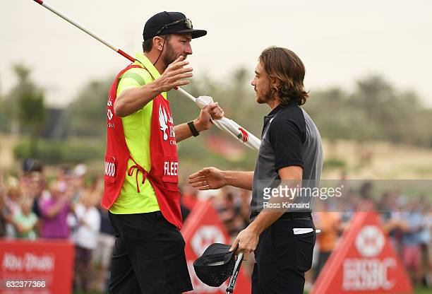 Tommy Fleetwood of England is congratulated by his caddie after his birdie on the 18th green during the final round of the Abu Dhabi HSBC...